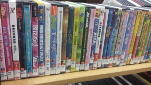 Childrens videos waiting to be cased and shelved.